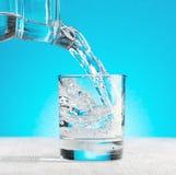 Bevattna att hälla in i ett exponeringsglas på blå bakgrund Fotografering för Bildbyråer