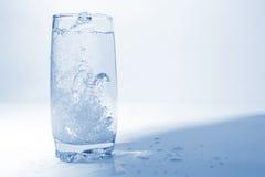 Bevattna att hälla i genomskinligt exponeringsglas med bubblor av luft Royaltyfria Foton