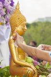 Bevattna att hälla och den förgyllda Buddhastatyn i den trad Songkran festivalen Royaltyfri Bild
