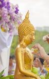 Bevattna att hälla och den förgyllda Buddhastatyn i den trad Songkran festivalen Royaltyfria Foton