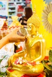Bevattna att hälla till Buddhastatyn i den Songkran festivalen av Thailand Arkivfoto