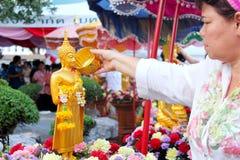 Bevattna att hälla till Buddhastatyn i Songkran festivaltradition Arkivbilder