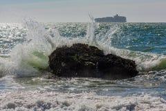 Bevattna att krascha in i vaggar med fartyget i bakgrund Royaltyfria Bilder