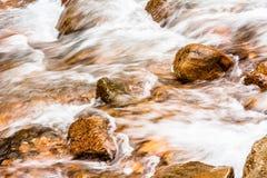 Bevattna att rusa över floden vaggar Arkivbild