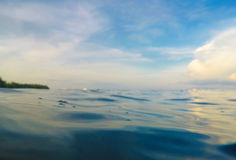 Bevattna bakgrund med vattenlinje, den tropiska ön för molnig himmel Dubbelt landskap med havet och himmel Royaltyfria Bilder