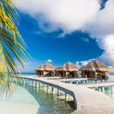 Bevattna bungalower med härlig blå himmel och havet i Maldiverna arkivfoton