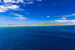 Bevattna bungalower med härlig blå himmel och havet i Maldiverna royaltyfri bild