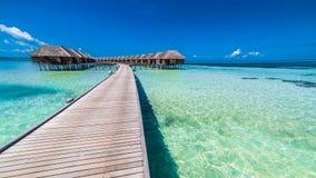 Bevattna bungalower med härlig blå himmel och havet i Maldiverna royaltyfri foto