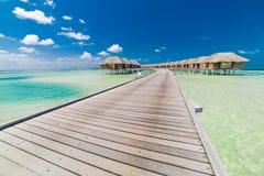 Bevattna bungalower med härlig blå himmel och havet i Maldiverna royaltyfria foton