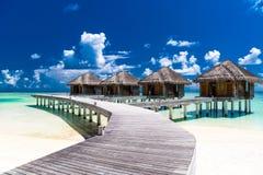 Bevattna bungalower med härlig blå himmel och havet i Maldiverna fotografering för bildbyråer