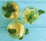 Bevattna den nya citronen, drink för sommar för bakgrund för uppfriskande lemonad för mintkaramell hemlagad blå trä royaltyfria bilder