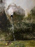 Bevattna flöde ut ur röret av gamla cementvattenbehållare Arkivfoto