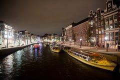 Bevattna gatan med fartyg och byggnader vid natt i Amsterdam Arkivbild