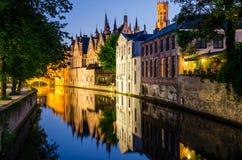 Bevattna kanalen, medeltida hus och klockatornet på natten i Bruges Royaltyfri Foto