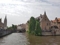 Bevattna kanalföljden i Bruges med gamla byggnader Arkivbild
