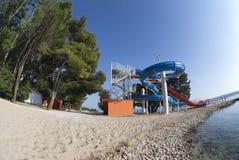 Bevattna parkerar och sörjer träd på sandstranden i Crikvenica Arkivbilder