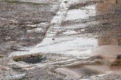 Bevattna skada till vägen från bristningen som läcker vattenröret arkivbild