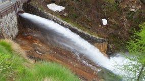 Bevattna urladdning från fördämningen av sjön Fregabolgia en alpin konstgjord sjö arkivfilmer