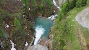 Bevattna urladdning från fördämningen av sjön Fregabolgia en alpin konstgjord sjö stock video