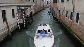 Bevattna utfärden, den motoriska skytteln med turister seglar längs kanalen mellan hus stock video