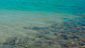 Bevattna yttersida- och krusningsvågor i det stillsamma havet med stenar på sandig botten Blått vatten i det lugna havet och sten stock video