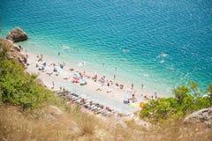 Bevattnar den tropiska stranden för härlig sommar med azurer havet och många vila personer Royaltyfria Bilder
