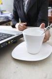Beve il caffè durante il lavoro Immagini Stock
