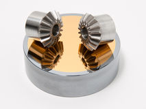 Bevel gear-wheels. On a golden mirror isolated against a white background stock photo