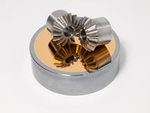 Bevel gear-wheels. On a golden mirror isolated against a white background stock photography