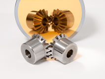 Bevel gear-wheels. Before a golden mirror isolated against a white background stock photography