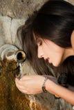 Bevendo da un pozzo d'acqua Immagine Stock