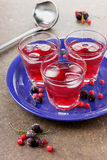 Beverage from berries. With ice cubes and black and red currant on a blue ceramic dish Stock Photos