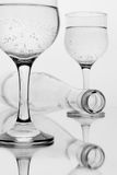 Beverage with bubbles. Black and white photo of beverage with bubbles. Wineglasses and lying bottle with a sparkling bubbly drink Stock Photo