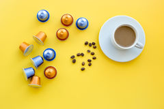 Beverage capsules for coffee mashine near coffee cup and grains on yellow background top view copyspace Royalty Free Stock Photos