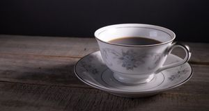 Beverage in fine china tea cup. On wooden table and black background Stock Photography