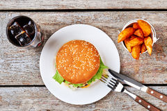 Beverage, fries, hamburger on plate. Cutlery and bucket of fries. Tasty recipe of burger Royalty Free Stock Image