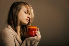 Beverage. Girl holding cup mug of hot drink tea or coffee. Hot beverage. Sleepy girl holding cup mug of drink tea or coffee. Woman in warm sweater warming stock images