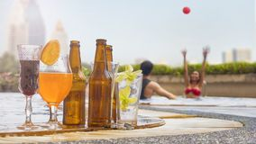 Beverage and juice drink with exotic cocktails and bottle of bee. The beverage and juice drink with exotic cocktails and bottle of beer set up on the swimming stock photography