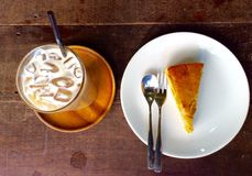 Beverage served with pumpkin pie. Ice coffee on the table with pumpkin pie served royalty free stock photos