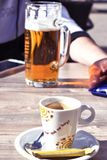 Beverages in a cafe. Beverages in cafe. Espresso coffee and biscuit with pint of beer in daylight Royalty Free Stock Images