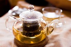 Beverages, good morning and breakfast concept - Cup of white green tea and teapot on the table stock photography