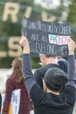 We are all American we belong here sign. BEVERLY HILLS, CALIFORNIA - MARCH 12, 2018: A protester holds a sign `Immigrant, Muslim, POC, Queer. We are all American Stock Photo