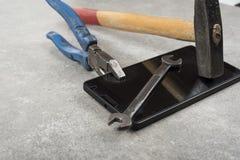 Bevestig uw mobiele telefoon met hamerpaar van buigtang of een moersleutel niet stock fotografie