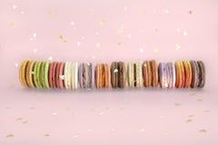 Bevinden de cake Franse makarons zich, zoete kleurrijke macarons in rij en gouden confettien op lichtrose achtergrond De partij v royalty-vrije stock afbeelding