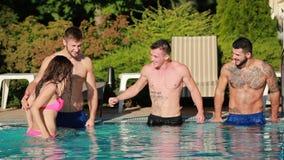 Bevinden jonge mens zich drie en het mooie meisje in het zwembad en tonen duimen stock videobeelden