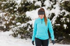 Bevindend meisje die de wintersportkleding, bomenachtergrond dragen Stock Foto's