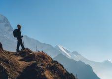 Bevindende jonge vrouw op de heuvel en het kijken op bergen stock afbeeldingen