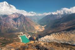 Bevindende mensen met rugzakken op de bergpiek stock afbeelding