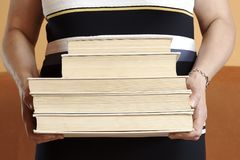 Bevindende rijpe vrouw die een stapel boeken houden stock fotografie