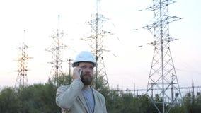 Bevindt de post technische directeur zich in een witte helm dichtbij de krachtcentrale en het spreken op de telefoon met de arbei stock footage